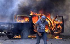 Protesters set fire to police vehicles during clashes with riot police along a road which leads to the U.S. embassy, near Tahrir Square in Cairo September 13, 2012. Egypt's President Mohamed Mursi said on Thursday he supported peaceful protest but not attacks on embassies, after Egyptians angry at a film deemed insulting to the Prophet Mohammad climbed into the U.S. embassy in Cairo and tore down the U.S. flag. He pledged to protect foreigners in Egypt. REUTERS/Mohamed Abd El Ghany