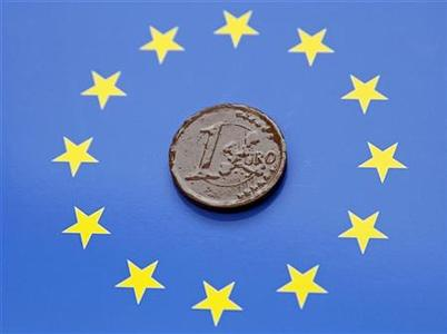 A one Euro coin made of chocolate is displayed on a Euro flag in this photo illustration taken in Ljubljana September 11, 2012. REUTERS/Srdjan Zivulovic