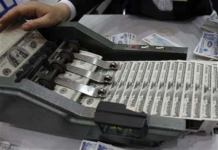 A staff counts U.S. dollar banknotes at the Vietcombank's headquarters in Hanoi April 6, 2012. REUTERS/Kham/Files