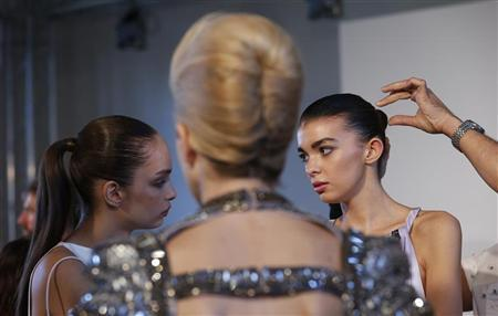 A model has her hair styled before a reception on the eve of London Fashion Week September 13, 2012. REUTERS/Suzanne Plunkett
