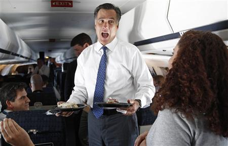 U.S. Republican presidential nominee and former Massachusetts Governor Mitt Romney reacts as he is presented with cake from a member of the media who celebrated her birthday on the campaign plane on the way to Long Island, New York September 13, 2012. REUTERS/Jim Young