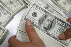 Сотрудник Korea Exchange Bank пересчитывает банкноты по 100 долларов в банке в Сеуле, 6 января 2010 года. Курсы доллара к евро и швейцарскому франку упали до минимума четырех месяцев после объявления новых стимулирующих мер центробанка США. REUTERS/Choi Bu-Seok