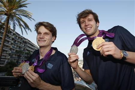 France Olympic swimming champions and medallists Yannick Agnel (L) and Clement Lefert display their medals as they celebrate while riding on double-deck bus during their arrival in Nice August 10, 2012. REUTERS/Eric Gaillard