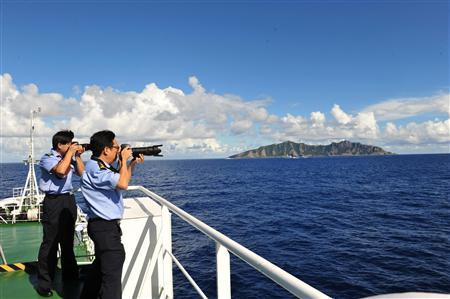 Crew members of China's surveillance ship Haijian 50 takes pictures as they sail on waters near the disputed islands, called Senkaku in Japan and Diaoyu in China, in the East China Sea September 14, 2012 in this picture distributed by Chinese official Xinhua News Agency. REUTERS/Xinhua/Zhang Jiansong