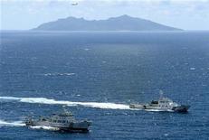 Китайский военный корабль (слева) и судно, принадлежащее японской береговой охране, плывут в территориальных водах рядом с островами в Восточно-Китайском море, 14 сентября 2012 года. Шесть китайских военных кораблей ненадолго вошли в пятницу в территориальные воды рядом с островами в Восточно-Китайском море, что встретило резкую ответную реакцию в Японии, также претендующей на эти земли. REUTERS/Kyodo