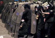 Polícia anti-choque protege-se de pedras atiradas por manifestantes durante confrontos no caminho que leva à embaixada norte-americana, perto da Praça Tahrir, no Cairo. 13/09/2012 REUTERS/Mohamed Abd El Ghany