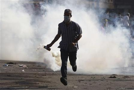 A protester throws a tear gas canister, which was earlier thrown by riot police, during clashes along a road leading to the U.S. embassy, near Tahrir Square in Cairo September 14, 2012. Egyptian protesters, angry at a film they say insults Prophet Mohammad, hurled stones on Friday at a line of police in Cairo blocking their way to the U.S. embassy, which was attacked earlier this week. REUTERS/Amr Abdallah Dalsh