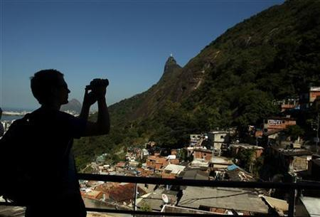 A tourist takes pictures at the Santa Marta slum in Rio de Janeiro, September 5, 2012. REUTERS/Pilar Olivares