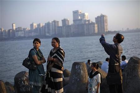 People walk at a seafront promenade in the evening at the Nariman Point financial area in south Mumbai March 15, 2012. REUTERS/Vivek Prakash
