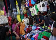 People shop for clothes at a roadside store at a market in Mumbai September 14, 2012. India opened its supermarkets to foreign direct investment and allowed foreign airlines to invest in local carriers in a spate of reform initiatives on Friday, a day after New Delhi raised the price of heavily subsidised diesel. REUTERS/Danish Siddiqui