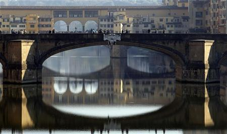 People stroll downtown Florence November 20,2011. Italian newspapers said on Sunday that new budget measures were likely to be unveiled within two weeks, with a property tax abolished by Berlusconi set to return, plus moves to tackle tax evasion and a cut in payroll taxes to lift employment. REUTERS/Giampiero Sposito
