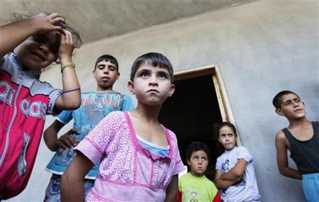 Syrian refugees stand where they are staying temporarily with their relatives at a school in Wadi Khaled town, near the Syria border in north Lebanon July 24, 2012. REUTERS/Jamal Saidi