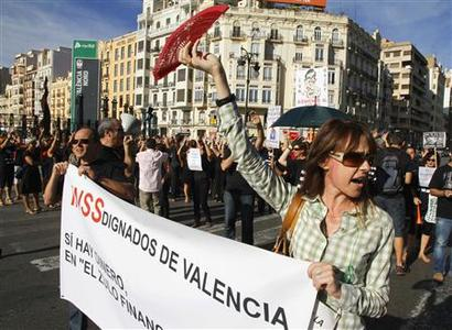 A woman shouts slogans during a civil servants' protest against cuts in public services in Valencia, September 14, 2012. The banner reads: ''Indignants of Valencia - there is money, in the banks' hiding place''. REUTERS/Heino Kalis