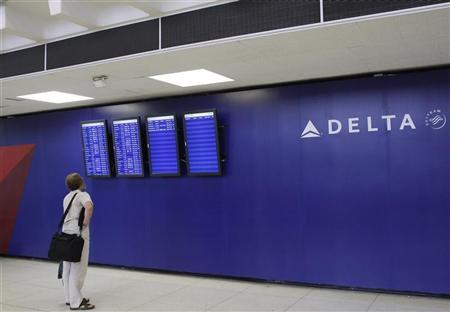 A man looks at a monitor for arrival and departure flight information at the Delta airline terminal at JFK Airport in New York, July 30, 2008. REUTERS/Joshua Lott