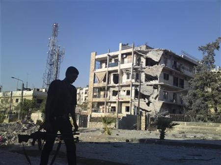 A member of the Free Syrian Army walks near a damaged building in Aleppo September 2, 2012. REUTERS/Shaam News Network/Handout