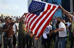 Manifestantes na Tunísia queimam bandeira norte-americana em protesto do lado de for a da embaixada dos EUA, em Túnis. A fúria sobre um filme que insulta o profeta Maomé se espalhou pelo Oriente Médio, com manifestantes atacando embaixadas dos EUA e queimando bandeiras norte-americanas. 12/09/2012 REUTERS/Zoubeir Souissi