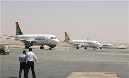 Airport personnel walk in the tarmac after Benghazi airport was re-opened September 14, 2012. REUTERS/Stringer