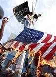 Портестующие сжигают флаг США у американского посольства в Тунисе 12 сентября 2012 года. Волна ярости из-за фильма о пророке Мухаммеде прокатилась по Ближнему Востоку в пятницу - толпы взбешенных людей атаковали посольства США и жгли американские флаги, заставив Пентагон усилить меры безопасности в дипломатических представительствах страны. REUTERS/Zoubeir Souissi