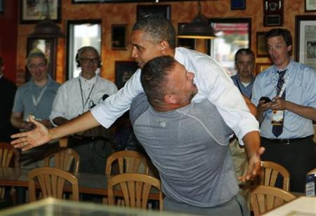 U.S. President Barack Obama holds on as he is hugged and picked up by Scott Van Duzer at Big Apple Pizza and Pasta Italian Restaurant in Fort Pierce, Florida, while campaigning across the state by bus, September 9, 2012. REUTERS/Larry Downing