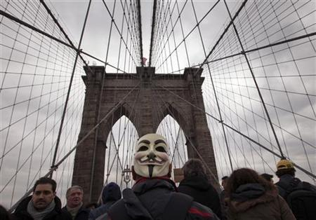A Occupy Wall Street activist, wearing a mask, takes part in a march across the Brooklyn Bridge in New York April 1, 2012. REUTERS/Adrees Latif