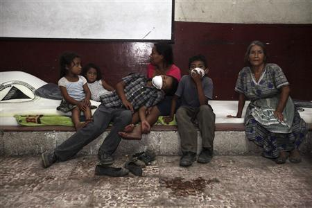 A family sit together at a shelter after being evacuated from their home in Santa Lucia Cotzumalguapa, 90 km (56 miles) south of Guatemala City, September 13, 2012. REUTERS/William Gularte