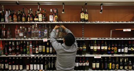 A shop owner removes bottles of hard liquor from a shelf in Prague September 14, 2012. The Czech Health Ministry on Friday indefinitely banned the sale of drinks containing more than 20 percent alcohol after 19 people died from drinking bootleg spirits containing poisonous methanol, the CTK news agency reported. REUTERS/David W Cerny