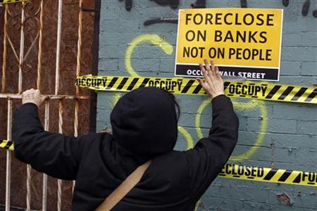 An Occupy Wall Street demonstrators pastes tape and signs to a foreclosed property in the East New York section of Brooklyn in New York City December 6, 2011. REUTERS/Mike Segar