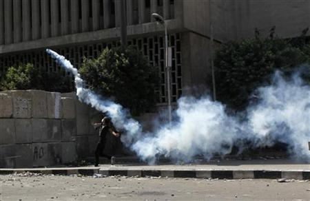 A protester throws a tear gas canister back to the police, during a demonstration, condemning a U.S.-made film which they say insults the Prophet Mohammad, near the U.S. embassy in Cairo, September 14, 2012. REUTERS/Asmaa Waguih