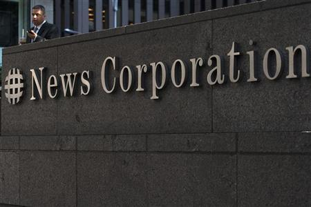 A passer-by stands in front of the News Corporation building in New York June 28, 2012. News Corp said on Thursday its board had approved a plan to split the company into two entities, and that Rupert Murdoch will remain as chief executive of its new, separate entertainment company. REUTERS/Keith Bedford