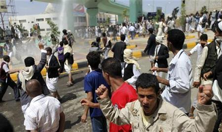 Protesters run as police use water cannons to disperse them at a crossroad leading to the U.S. embassy in Sanaa September 14, 2012. REUTERS/Mohamed al-Sayaghi