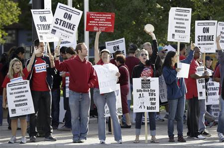 Members of the Chicago Teachers Union carry placards outside the Benito Juarez High School on the fifth day of their strike in Chicago September 14, 2012. REUTERS/John Gress