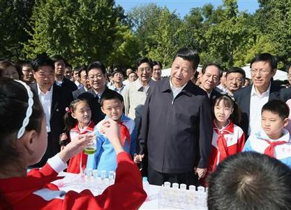 Chinese Vice President Xi Jinping (C) watches an experiment with children during an event marking the National Science Popularization Day at China Agricultural University in Beijing, September 15, 2012 in this picture distributed by Chinese official Xinhua News Agency. Chinese leader-in-waiting Xi appeared in public on Saturday for the first time in about two weeks, visiting a Beijing university. REUTERS/Xinhua/Lan Hongguang