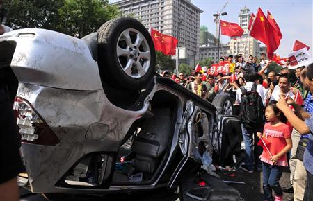 Demonstrators hold Chinese flags and banners beside an overturned car of a Japanese brand during a protest in Xi'an, Shaanxi province September 15, 2012. REUTERS/Rooney Chen