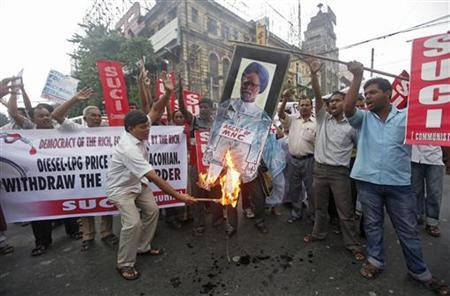 An activist from the Socialist Unity Centre of India (SUCI) burns a portrait of India's Prime Minister Manmohan Singh during a protest against rise in fuel prices and Foreign Direct Investment (FDI) in Kolkata September 15, 2012. REUTERS/Rupak De Chowdhuri