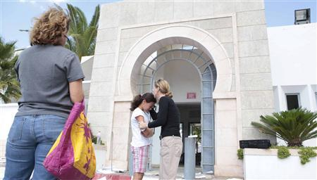 A teacher embraces a schoolgirl after witnessing the damage inside the American School after it was attacked by protesters in Tunis September 15, 2012. REUTERS/Zoubeir Souissi