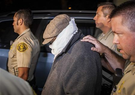 An unidentified person (C) is escorted out of Nakoula Basseley Nakoula's home by Los Angeles County Sheriff's officers in Cerritos, California September 15, 2012. Nakoula, a California man convicted of bank fraud is under investigation for possible probation violations stemming from the making of an anti-Islam video that has triggered violent protests against the U.S.in the Muslim world, U.S. officials said on Friday. REUTERS/Bret Hartman