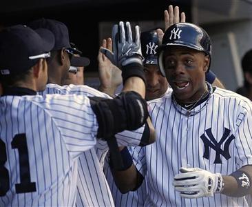 New York Yankees' Curtis Granderson (R) is congratulated by teammates after hitting a two-run home run against the Tampa Bay Rays during the second inning of their MLB American League baseball game at Yankee Stadium in New York, September 15, 2012. REUTERS/Adam Hunger