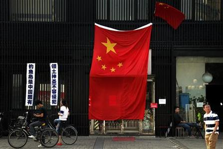 People look at a large Chinese national flag that covers the entrance to a Japanese restaurant located near the Japanese embassy in Beijing September 16, 2012. REUTERS/David Gray