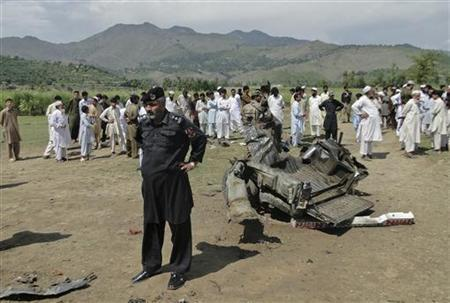 A security official and residents stand at the site of a bomb attack in Jandool, a town in the Lower Dir District of Pakistan's Khyber Pakhtunkhwa province September 16, 2012. REUTERS/ M. Abdullah