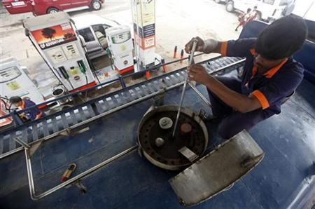 An employee measures diesel in a tanker before unloading at a fuel station in Kolkata August 13, 2012. REUTERS/Rupak De Chowdhuri