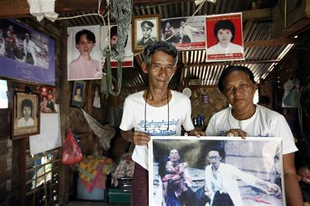 Win Kyu (L) and Khin Htay Win, father and mother of Win Maw Oo, hold a picture taken during the 1988 revolution in which their injured daughter is carried by two doctors, at their home in Yangon September 13, 2012. REUTERS/Stringer