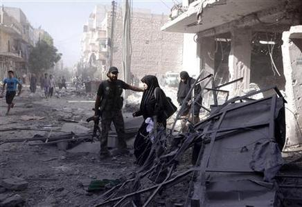 A member of the Free Syrian Army helps women as they leave a shelled building in Aleppo's district of al-Shaar September 16, 2012. REUTERS/Zain Karam