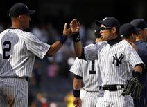 New York Yankees Derek Jeter (2) and Ichiro Suzuki celebrate their win against the Tampa Bay Rays in their MLB American League baseball game at Yankee Stadium in New York, September 16, 2012. REUTERS/Adam Hunger