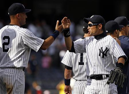 New York Yankees Derek Jeter (2) and Ichiro Suzuki celebrate their win against the Tampa Bay Rays in their MLB American League baseball game at Yankee Stadium in New York, September 16, 2012. REUTERS/Adam Hunger