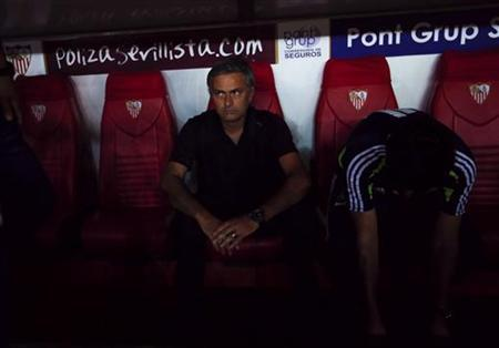 Real Madrid's coach Jose Mourinho sits before the start their Spanish First Division soccer match against Sevilla at Ramon Sanchez Pizjuan stadium in Seville September 15, 2012. REUTERS/Marcelo del Pozo