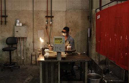 An employee prepares to weld a copper hose at the Sociedade Paulista de Tubos Flexiveis (SPTF) metallurgical company which manufactures flexible metal hoses, in Sao Paulo April 20, 2012. REUTERS/Nacho Doce