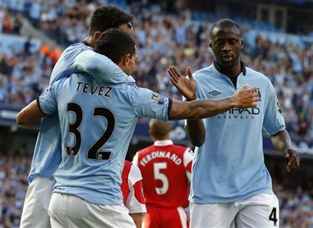 Manchester City's Yaya Toure (R) celebrates his goal against Queens Park Rangers with teammates Carlos Tevez (C) and Joleon Lescott during their English Premier League soccer match at The Etihad Stadium in Manchester, northern England September 1, 2012. REUTERS/Phil Noble