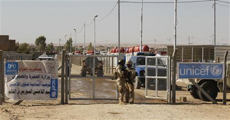 Iraqi army soldiers stand guard at a gate refugee camp in al-Qaim, Anbar province September 8, 2012. REUTERS/Thaier al-Sudani