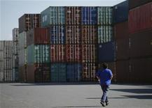 Мужчина проходит мимо грузовых контейнеров в порту в Токио, 10 сентября 2012 года. Один из крупнейших в РФ портовых операторов Global Ports заплатит акционерам промежуточные дивиденды в размере $47 миллионов или $0,3 на одну GDR, сообщила компания в понедельник. REUTERS/Toru Hanai