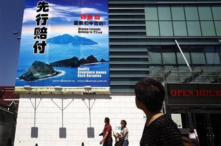 People look up at a large banner adorning the front of Beijing's Silk Street Market declaring that the famous knock-off designer wear store refuses 'to sell Japanese goods' due to issues over the disputed East China Sea islands in Beijing September 17, 2012. REUTERS/David Gray